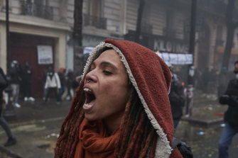 A protestor screams amidst clouds of tear gas and smoke.