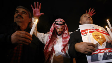 An activist wearing a mask depicting Saudi Crown Prince Mohammed bin Salman holds up his hands, painted with fake blood, as he protests the killing of Saudi journalist Jamal Khashoggi in Turkey.