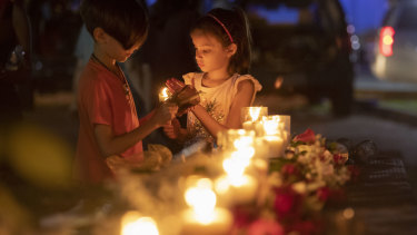 Local children light candles during a vigil held in the wake of the deadly school shooting in Santa Fe, Texas.