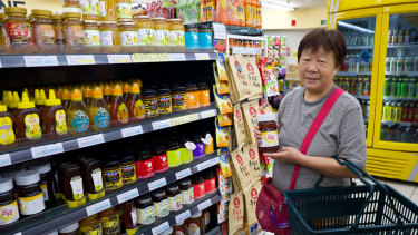 Beijing resident Ms. Yuan, 71, buys a jar of honey at Jingkelong Supermarket in Beijing. She says it improves her constipation.