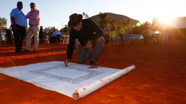 Noel Pearson signs a canvas on which the Uluru Statement from the Heart was later painted in May 2017.