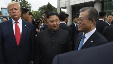 US President Donald Trump, left, North Korean leader Kim Jong-un, centre, and South Korean President Moon Jae-in, right, walk together at the border village of Panmunjom in Demilitarized Zone.