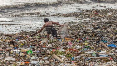A man collects plastic on the beach in Manila, the Philippines.