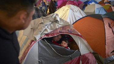 Ruth Aracely Monroy, centre, looks out of the family's tent alongside her 10-month-old son, Joshua, as her husband, Juan Carlos Perla, left, passes inside a shelter for migrants in Tijuana, Mexico. After fleeing violence in El Salvador and requesting asylum in the United States, the family was returned to Tijuana to await their hearing in San Diego last year.