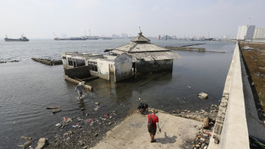 A former mosque is outside a giant sea wall in Jakarta. The city is slowly sinking.