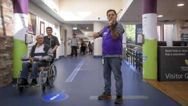 Musical reception: volunteer Jozsef Tallosi plays in the Footscray hospital foyer.
