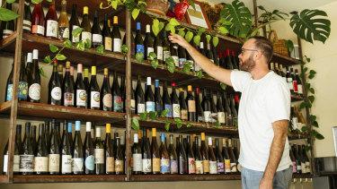 Madalenas owner Joel Rees straightens some wine.