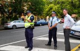 Assistant Commissioner Ben Marcus (centre) and Roads Minister Mark Bailey watching a routine speed camera operation outside Milton State School.