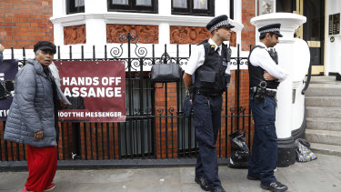 British police guard the Ecuadorian embassy as protesters supporting WikiLeaks founder Julian Assange hold a demonstration.