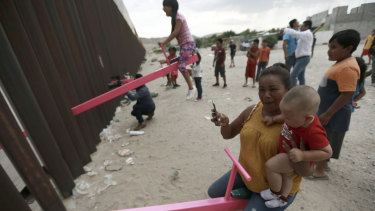 A mother and her baby play on a seesaw installed between the US and Mexico.