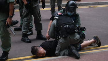 "A demonstrator is arrested by riot police during a protest in Hong Kong on Wednesday. China described Hong Kong's new security law as a ""sword of Damocles"" hanging over its most strident critics"
