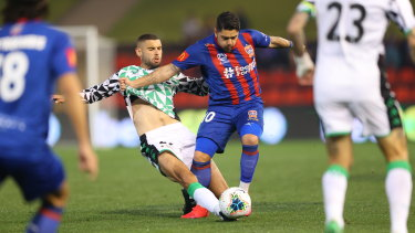 Timely intervention: Western's Tomislav Uskok defends bravely as Newcastle's Dimi Petratos surges forward.