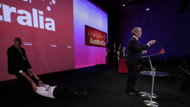 A protester is dragged off stage by security at Labor's national conference in Adelaide.