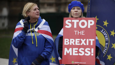 Anti-Brexit supporters hold placards outside Parliament on Monday.