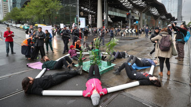 Extinction Rebellion protesters locked themselves together using plastic pipes to block Spencer and Collins streets..