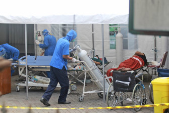 A medical worker wheels an oxygen tank to be used to treat patients at an emergency tent erected to accommodate a surge in COVID-19 cases, at Dr. Sardjito Central Hospital in Yogyakarta on Sunday.