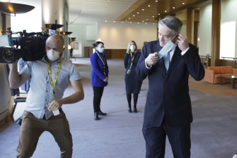 Finance Minister Mathias Cormann puts his mask back on after addressing the media.