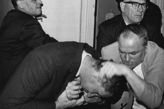 In a tangle ... Alderman A.A.C. Graham (light suit) scuffles with attendants who try to remove him from the meeting.