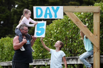 The Paddisons update their roadside isolation countdown sign in Kaipara Flats, Auckland, on Tuesday.