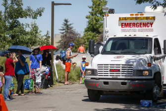 A Salvation Army vehicle is setup as a cooling station as people line up to get into a splash park to beat the heat in Calgary, Alberta.