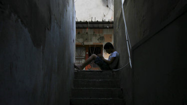 A boy reads on stairs in the Fatah area of Ain al-Hilweh.