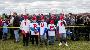 """From left, Matthew Sakowski, Dylan King, Evan Sakowski and Bryce King spell out the letters """"TRUMP"""" as they wait with other supporters to watch a Trump rally in Washington."""