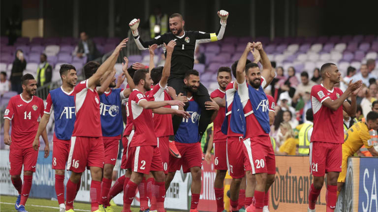 Huge result: Jordan's goalkeeper Amer Shafi, top, and his teammates celebrate their huge upset over the Socceroos.