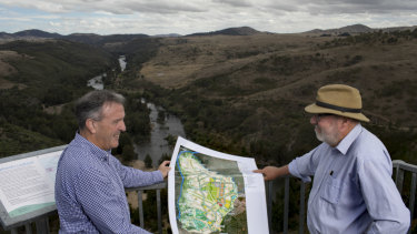 Riverview director David Maxwell, left, and consultant Tony Adam, at Shepherd's Lookout looking over the Murrumbidgee River and the area to the right to be developed for 11,500 homes and a conservation corridor. The pair, photographed in 2017, hold the development plan.