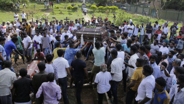 Sri Lankans prepare to bury the coffins carrying remains of Berington Joseph, left, and Burlington Bevon, who were killed in the Easter Sunday bombings.