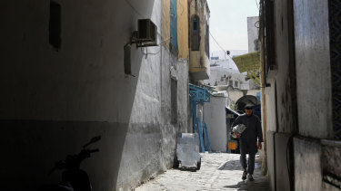 A man walks in an old alley, in the old city of Tunis, Tunisia.