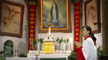 Members of the faithful attend a mass at the Cathedral of the Immaculate Conception, a government-sanctioned Catholic church in Beijing.