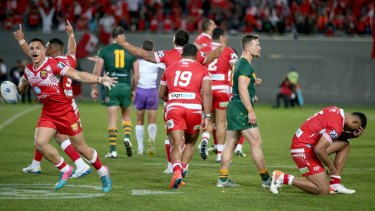 Tonga's players celebrate their victory as the full-time whistle sounds.