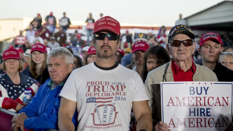 """A member of the audience wears a shirt that reads """"Proud to Be A Trump Deplorable"""" as President Donald Trump speaks at a rally at Southern Illinois Airport in Murphysboro, Illinois."""