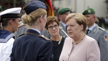 German Chancellor Angela Merkel and German Defence Minister Annegret Kramp-Karrenbauer, front second right, talk to soldiers during the ceremony in Berlin.