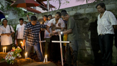 Relatives place flowers after the burial of three victims of the same family, who died at Easter Sunday bomb blast at St. Sebastian Church in Negombo, Sri Lanka.