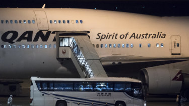 A Japanese worker wearing a protective suit stands next to a bus carrying Australians before boarding the Qantas plane for Darwin.