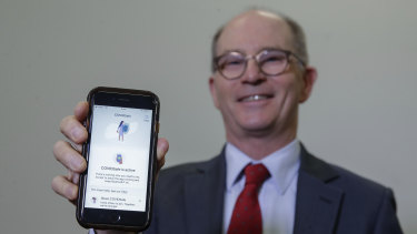 Deputy Chief Medical Officer Professor Paul Kelly poses with the COVIDSafe app downloaded to his mobile phone.