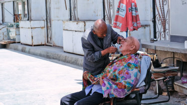 A street barber trims the beard of a man in the streets of Kashgar.