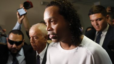 Former soccer star Ronaldinho is escorted by police.
