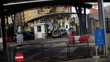 A Gibraltarian police officer talks with the driver of a car crossing the border of Spain with Gibraltar.