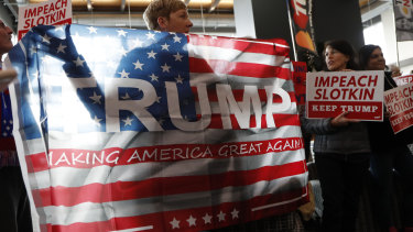 Waving the flag proudly: Donald Trump supporters gather before US Representative Elissa Slotkin holds a constituent community conversation at Oakland University in Michigan. Slotkin said she will vote to impeach Trump