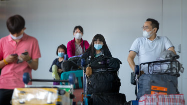 Visitors arrive at Melbourne Airport in wearing face masks.