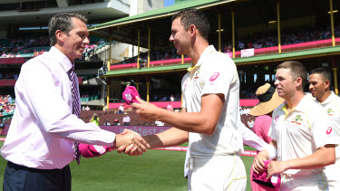 Glenn McGrath presents Josh Hazlewood and the Australian players with special caps for the Pink Test, which raise funds for the McGrath Foundation.