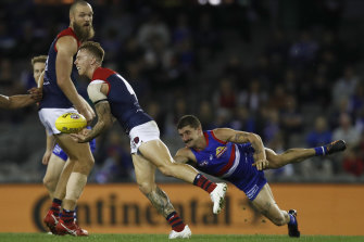 Melbourne's James Harmes looks to get the ball away under pressure from Tom Liberatore.