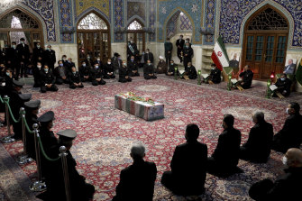 People pray over the flag draped coffin of Mohsen Fakhrizadeh.