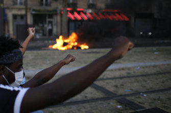 Protesters raise their fists during an unauthorised demonstration against police violence and racial injustice in Paris on Tuesday.