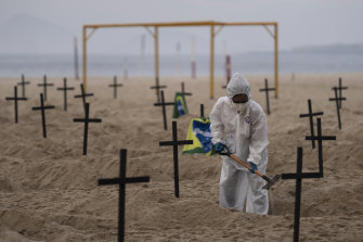 An activist digs symbolic graves on Copacabana Beach.