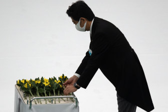 Japanese PM Shinzo Abe lays a flower during a memorial service marking the 75th anniversary of the end of World War II in Tokyo on Thursday.