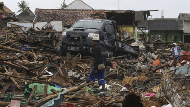 A tsunami survivor walks at a tsunami-ravaged village in Sumur, Indonesia.