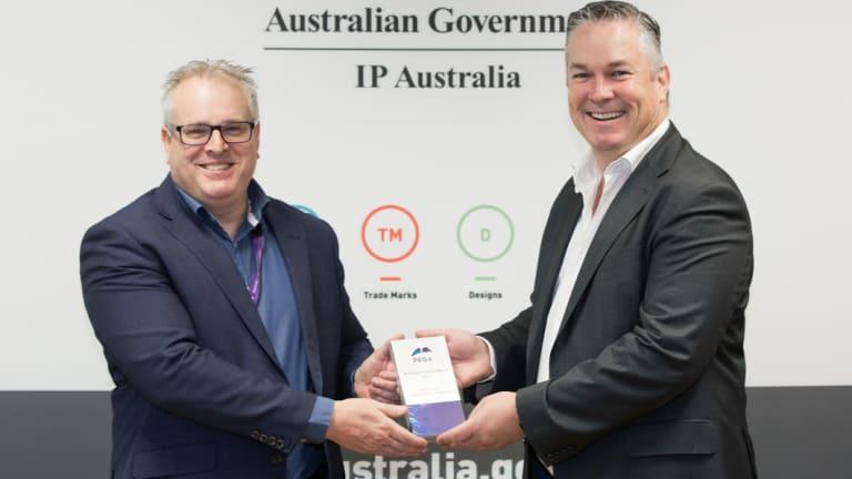 IP Australia general manager Robert Bollard receiving the award from Pegasystems's Luke McCormack.